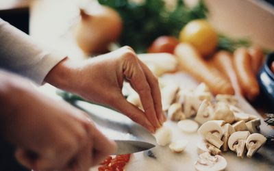 Woman's hands chopping up vegetables in kitchen
