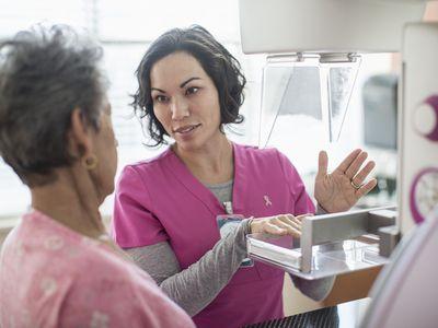 Technician explains mammogram to patient