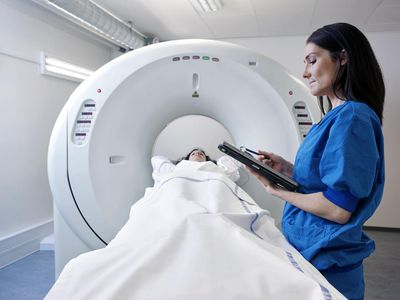 Nurse overlooking woman in CT-scanner