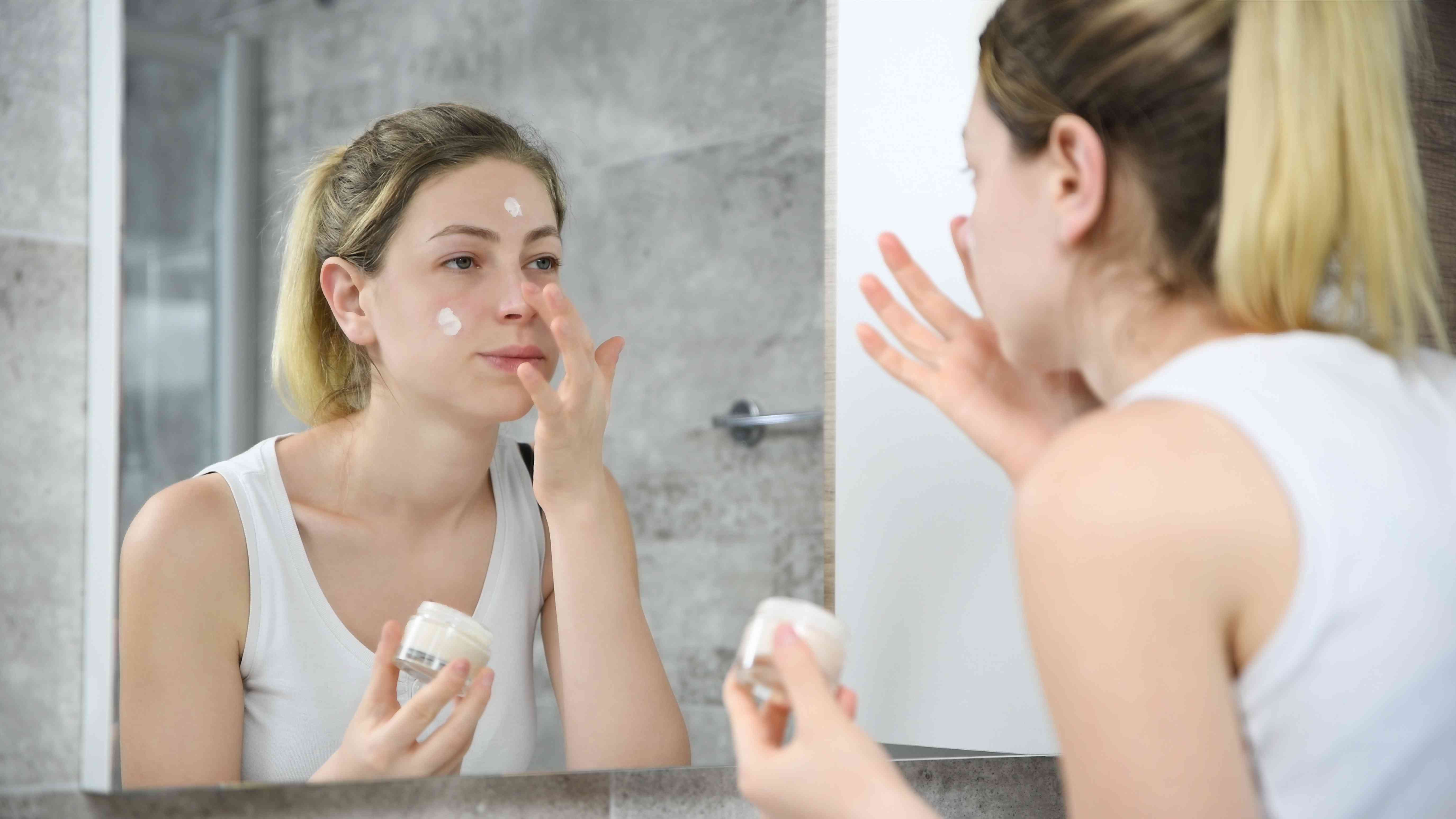 Young woman applying face cream in the mirror