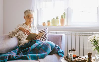 Woman reading on couch with blanket
