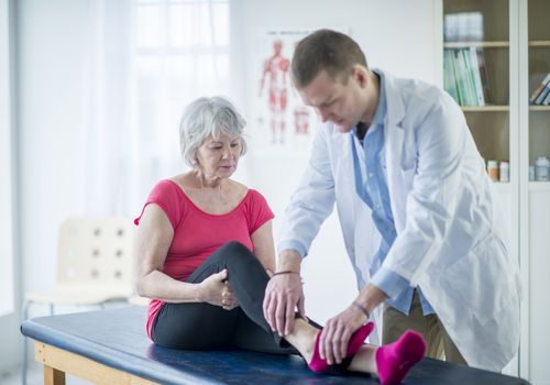Photo of a doctor looking at a senior woman's ankle