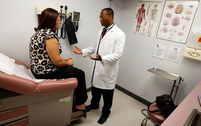 Woman discussing fibromyalgia and rheumatoid arthritis with doctor.