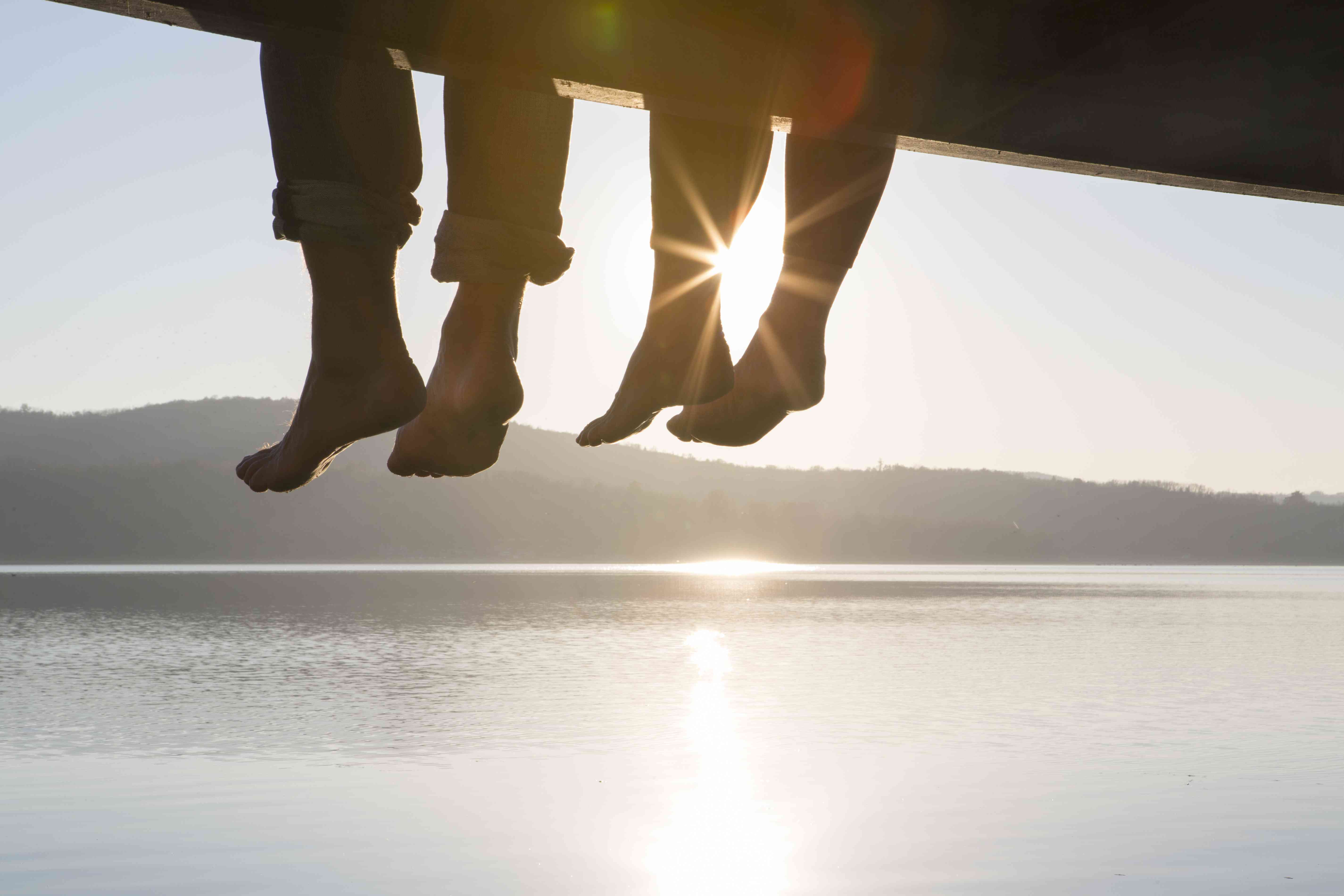 Feet dangling from dock with sun shining in background