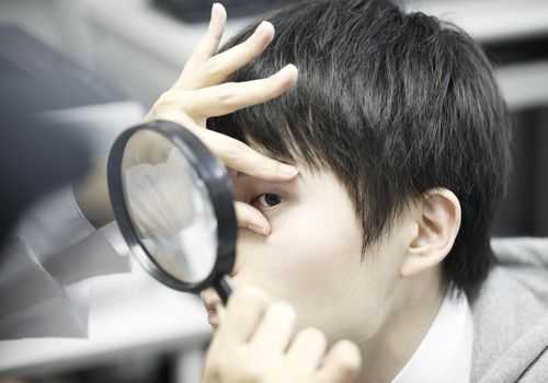 person looking at boy's eye with a magnifying glass