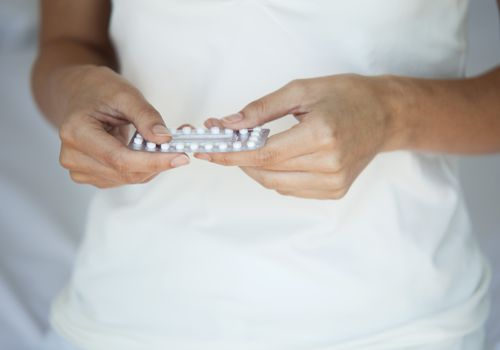 Woman holding birth control pills