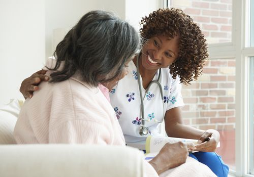 Photo of a healthcare professional showing a booklet to a senior woman