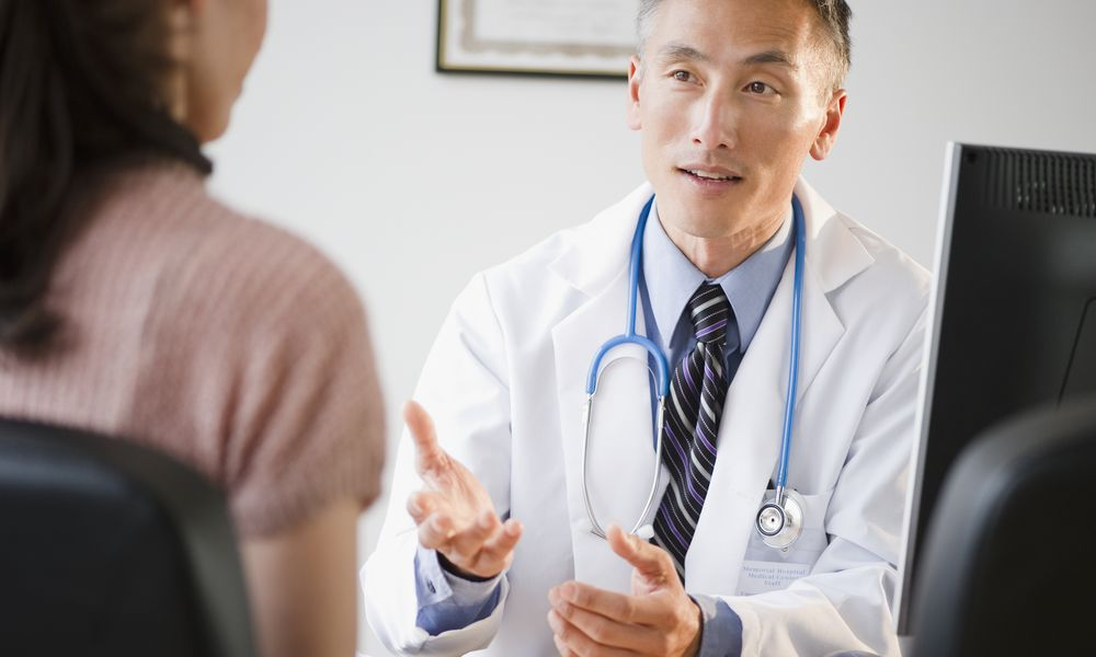 Doctor talking to female patient in his office