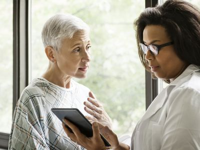 Female doctor explaining report to patient on digital tablet in clinic