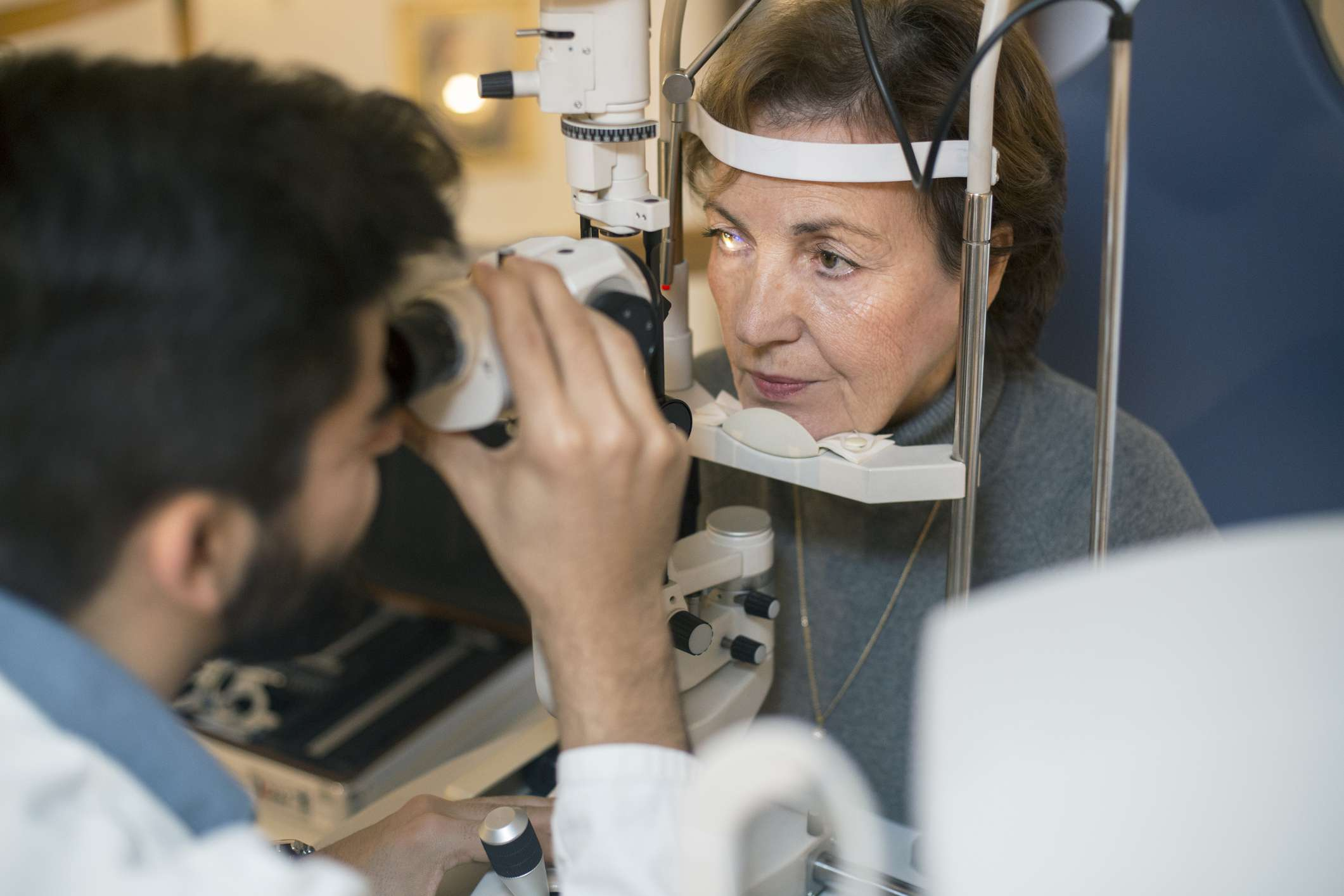 Senior woman during an eye testing with a male optometrist. About 35 years old doctor and about 60 years old female patient, both Caucasian.