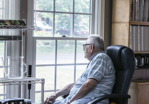 Older man forgetfully looking out the window