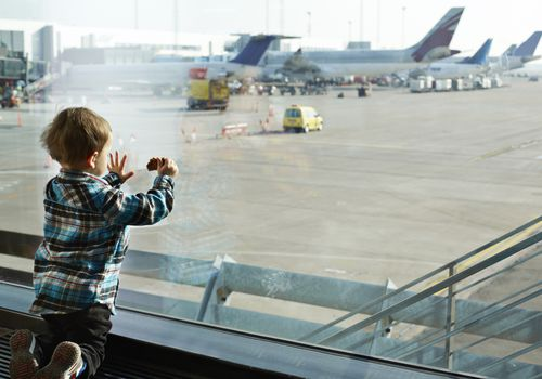 Small boy looking out of airport window