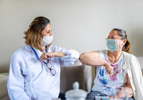 Medical provider bumping elbows with a patient, both wearing masks