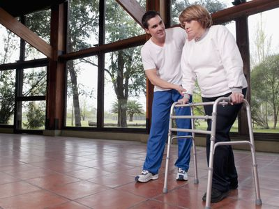 Photo of a woman and a PT with a walker.