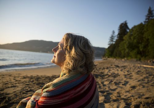 Serene woman wrapped in blanket on the beach sitting in the sunshine