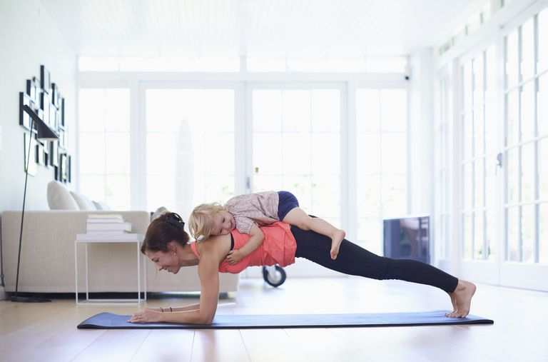 Photo of a woman doing a plank with a toddler on her back.