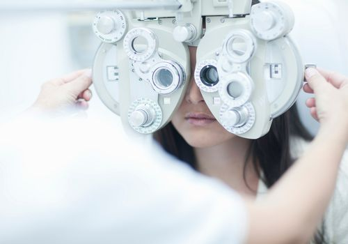 an eye doctor using a manual phoropter on a patient