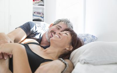 Smiling, affectionate couple cuddling in bed