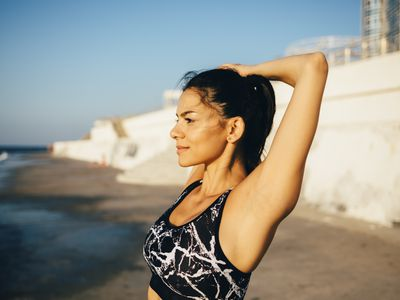 Woman during workout, stretching arm on the beach