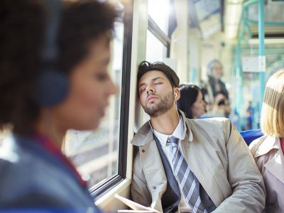 Businessman napping on train due to fatigue from infectious mononucleosis or the kissing disease