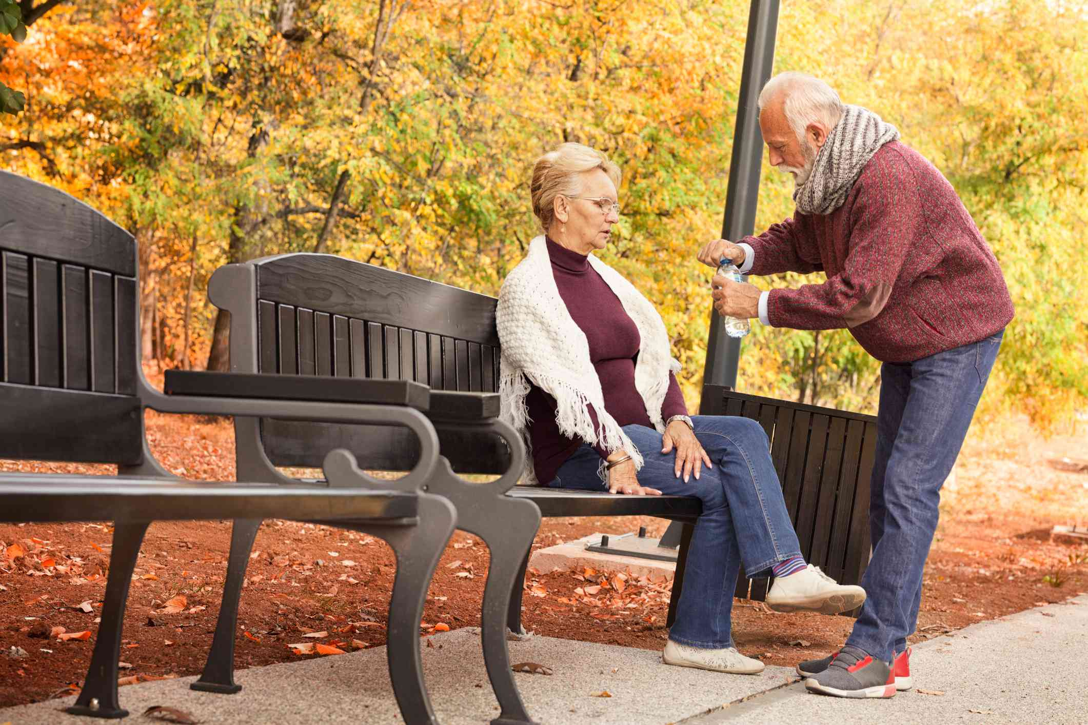 Woman sitting on a park bench while man opens water bottle for her