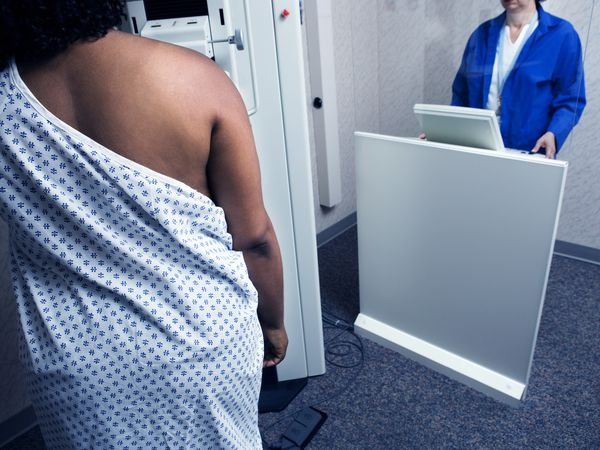 A Black woman with her back to the camera; she is wearing a hospital gown and having a mammogram.