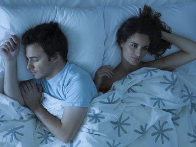 Woman awake in bed next to a sleeping man
