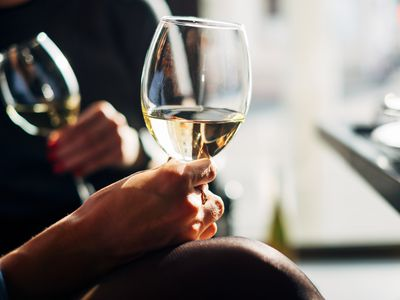 Two women sitting at a table enjoying a glass of wine - stock photo