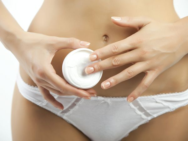 woman applying cream to belly