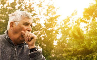 senior man coughing outside