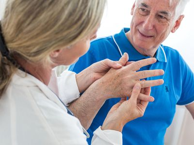 Doctor examines male hand for osteoarthritis.