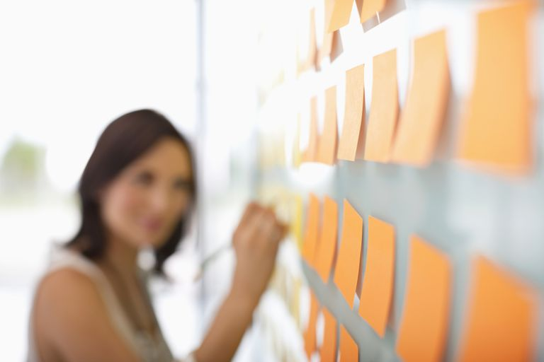 A woman writing on sticky notes