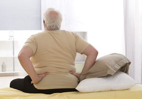 An overweight man sitting at the edge of his bed