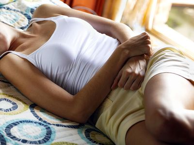Young woman in bed with PMS suffering