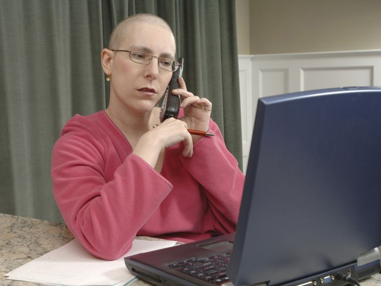 bald women in chemotherapy at her desk at work
