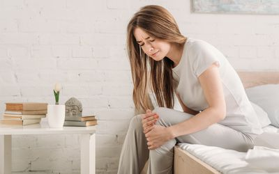 A woman sits on her bed, cradling her knee as though in pain