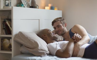 Male couple lying in bed together, face to face