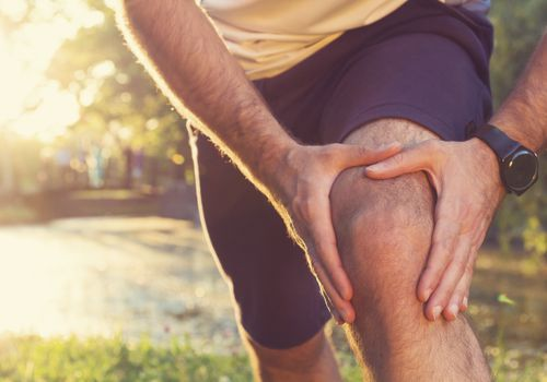 man holding a painful knee, knee pain can be a sign of lung cancer