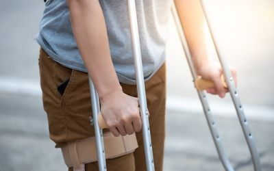 Disabled woman with crutches or walking stick or knee support standing in back side, half body