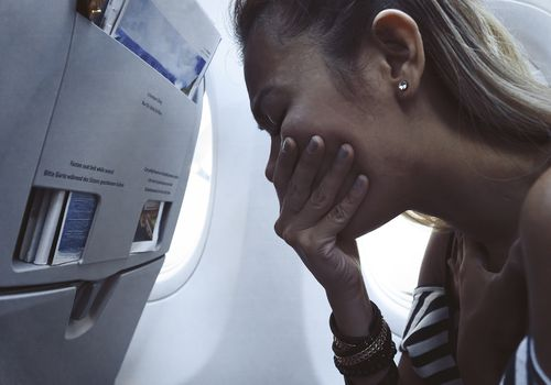 Woman on a plane feeling nauseous and covering her mouth