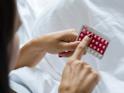 A woman looking at her birth control pills