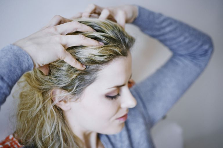 woman itching her scalp with fingers