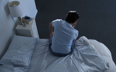 Man sitting on edge of bed