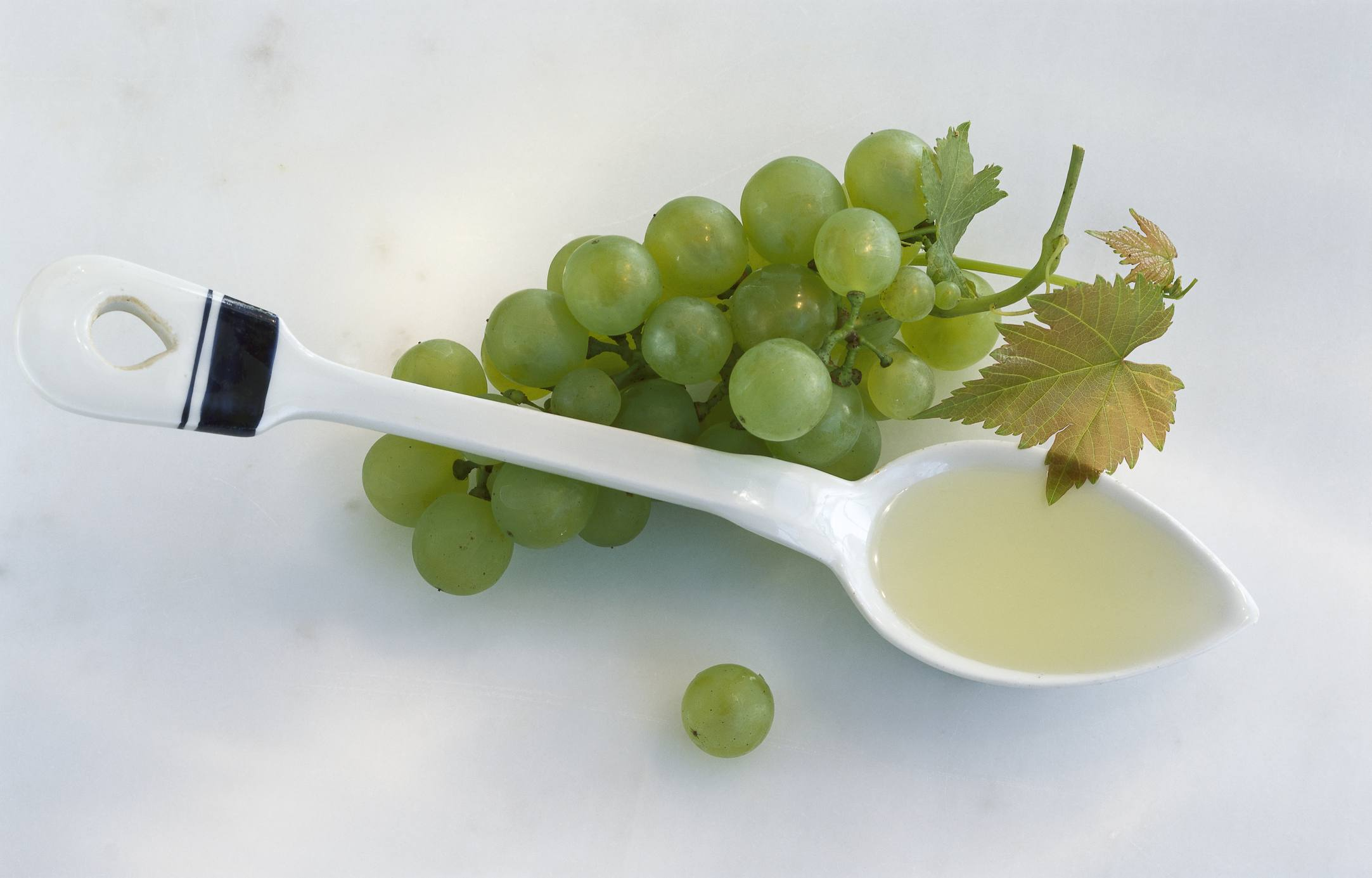Grape seed oil in a spoon next to grapes