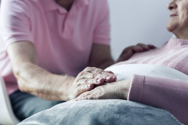 Man holding elderly woman's hand
