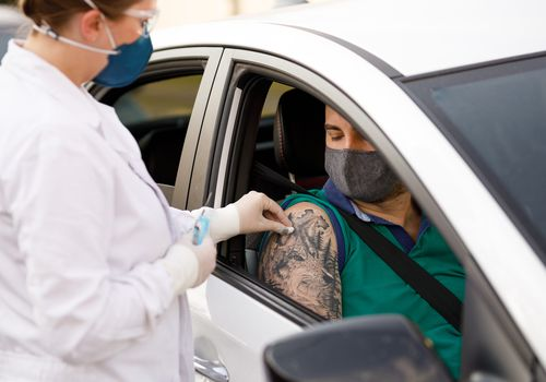 Man receiving vaccine from inside his car.