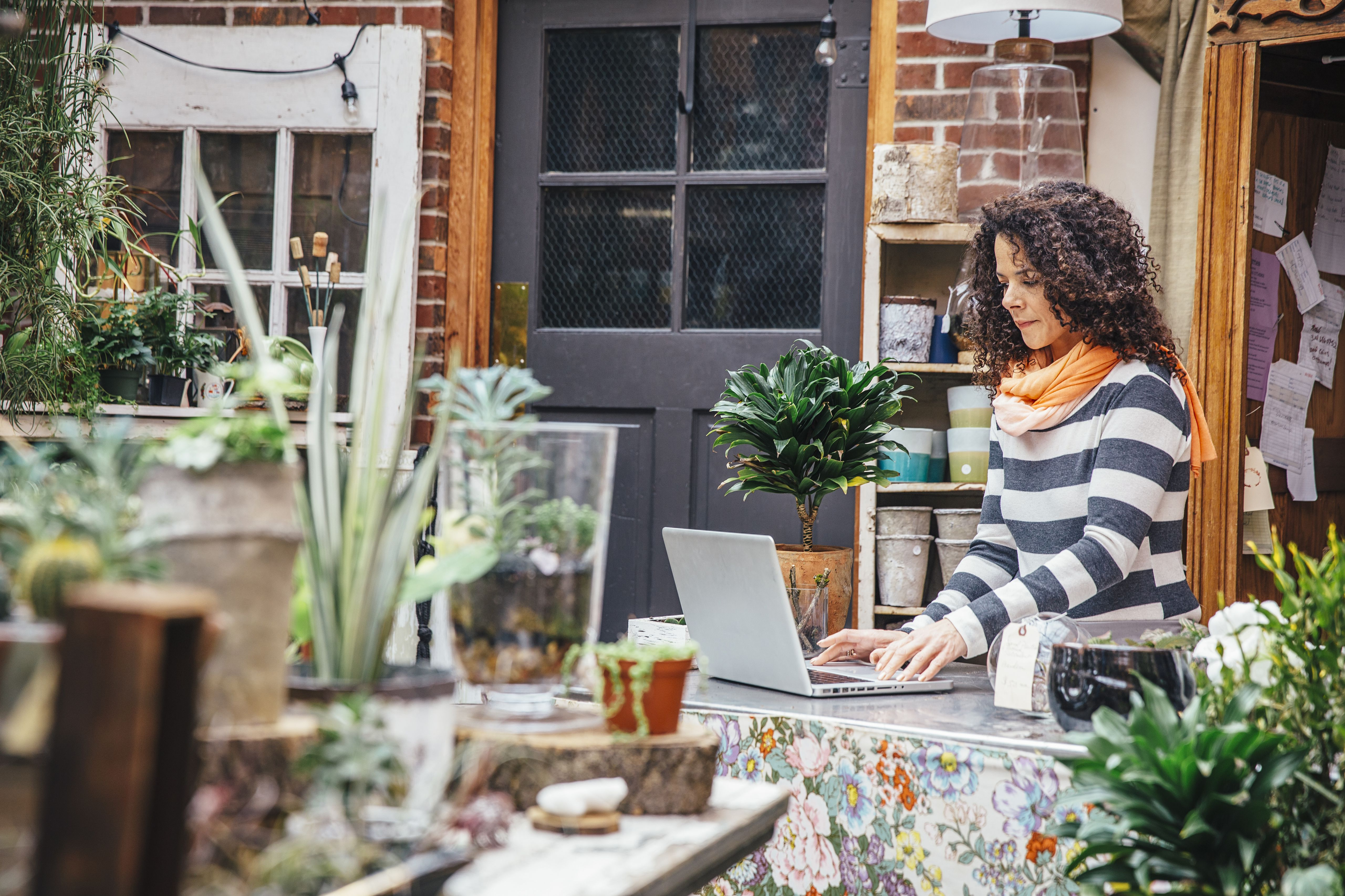 Woman on computer surrounded by plants