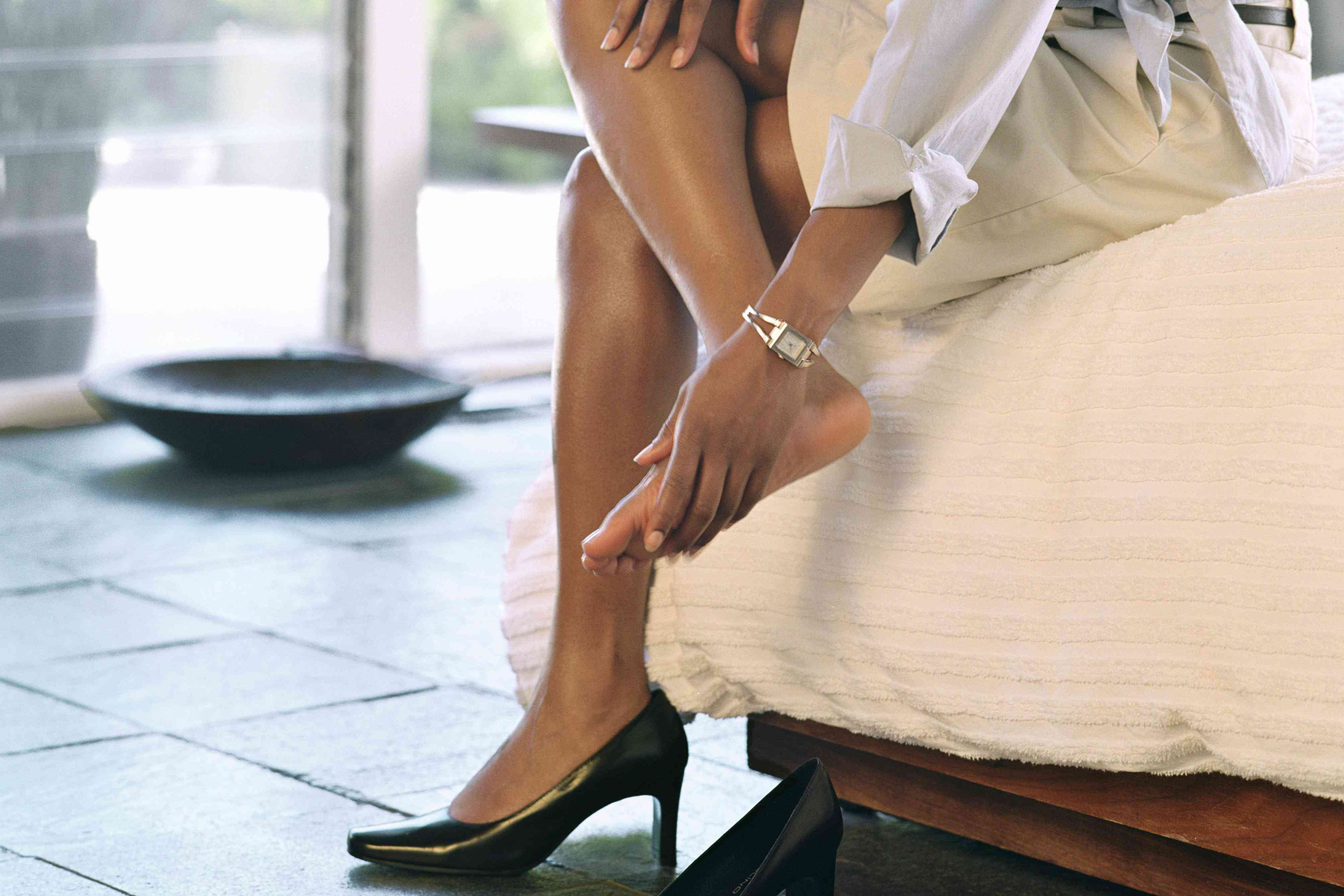 Woman with one high heel off rubbing her foot