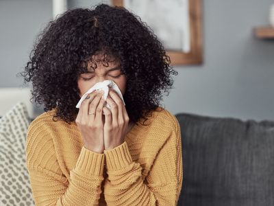 A woman with dark, curly hair sneezes into a tissue