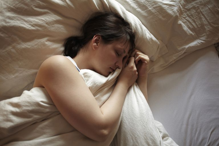 A woman sleeping in bed who may be experiencing hypnagogic jerks or sleep starts